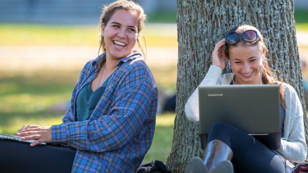 closeup, 2 girls laughing beneath tree